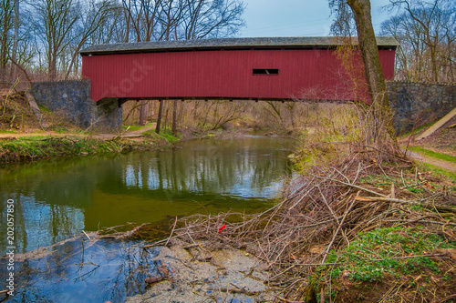 Outdoor view of red covered bridge inside of the forest over a small river in Lancaster