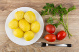 Boiled potatoes in plate, parsley, tomatoes and fork on table - 202060814
