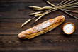 Fresh bread concept. Crispy french baguette near ears of wheat and bowl with flour on dark wooden background top view