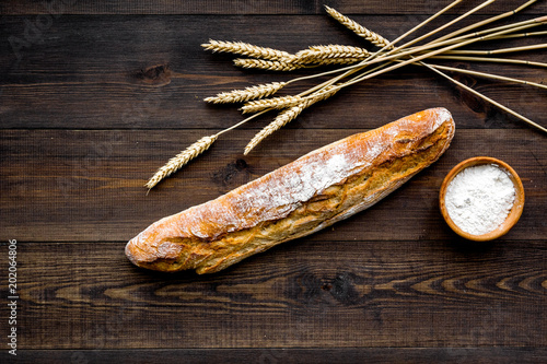 Fresh bread concept. Crispy french baguette near ears of wheat and bowl with flour on dark wooden background top view - 202064806