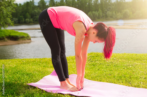 Yoga in park. Yoga girl pose practicing outdoors. Concept of healthy lifestyle