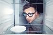 Student schaut in einen leeren Kühlschrank