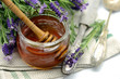 Lavender honey in a glass with flower pot of Lavandula stoechas and antique silverware.
