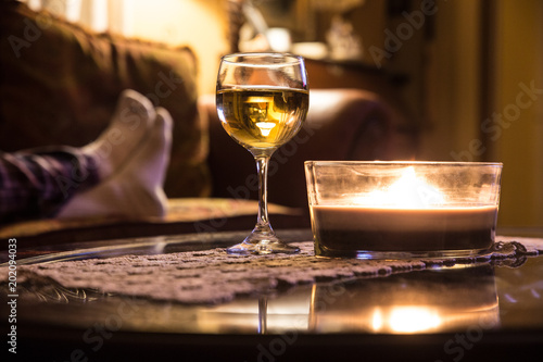 Wine glass and candle in a relaxing scene with persons feet on couch in the background - 202094033