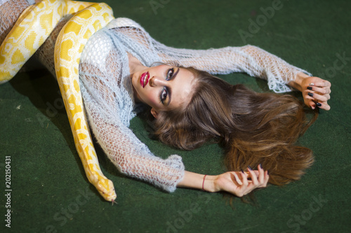Sensual woman relax with albino python. Snake crawl on woman with long hair. Beauty model with makeup face and yellow serpent. Danger temptation and desire concept © tverdohlib