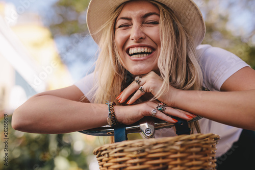 obraz lub plakat Attractive woman laughing outdoors with her bike