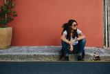 Female traveler resting on the sidewalk - 202159225