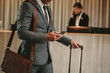Businessman in hotel lobby with phone and luggage