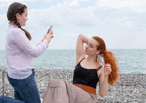 two girls on the beach with a phone on a sunny day