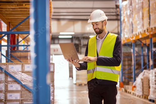 Modern device. Happy cheerful man holding a laptop while using in for doing the inventory in the warehouse