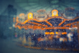 Rainy carousel through wet glass / window. Moody / retro styled and colored bacground photo - 202192840