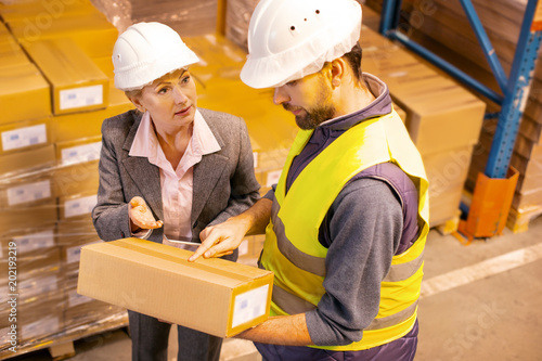 Global trade. Serious delivery man pointing at the box while talking to his manager