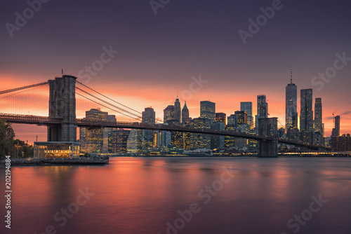Famous Brooklyn Bridge in New York City with financial district - downtown Manhattan in background. Sightseeing boat on the East River and beautiful sunset over Jane's Carousel. - 202194884