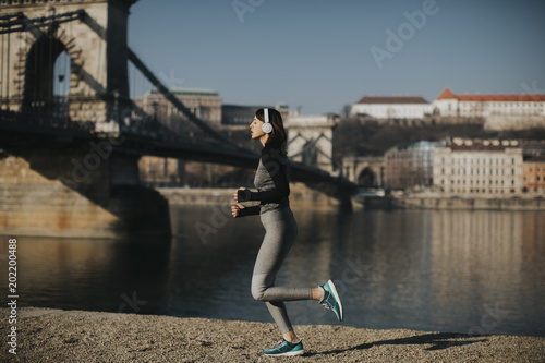 Canvas Boedapest Woman in sportswear running on Danube river promenade in Budapest