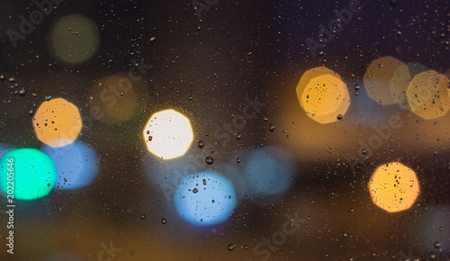 Fotobehang Heelal The background with the city lights at night with water drops on glass