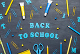 Back to school text with colorful stationary over the blackboard background