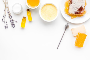 Homemade cosmetics with honey. Handmade soap, spa salt, cream on white background top view copy space