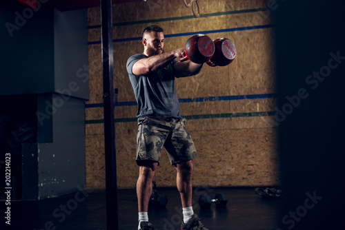 Fototapeta Close up above view of strong motivated and focused muscular bearded short hair bodybuilder man holding two large red kettlebells in front while training in the dark gym.