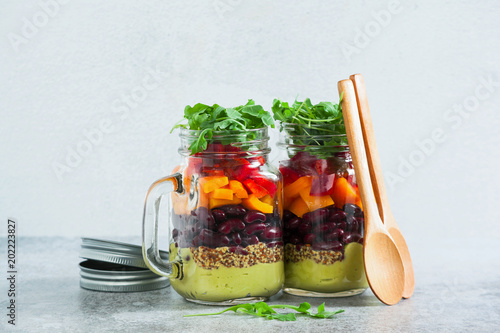 rainbow colored salad in jars on the table. with beans, fresh vegetables and avocado dressing with lime juice and mustard. copy space. © irinagrigorii