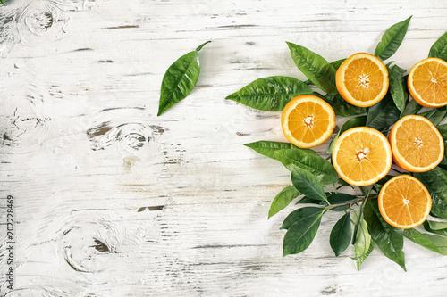 Połówki rżnięta pomarańczowa owoc i liść na rocznika drewnianym tle