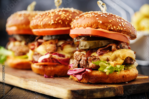 Fototapeta Homemade delicious juicy burger with beef, cheese, tomato and caramelized onion and potato balls.