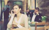 upset girl holding mobile in the restaurant - 202240844