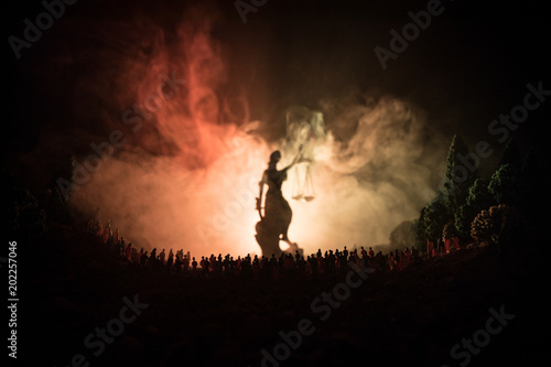 Silhouette of blurred giant lady justice statue with sword and scale standing behind crowd at night with foggy fire background.