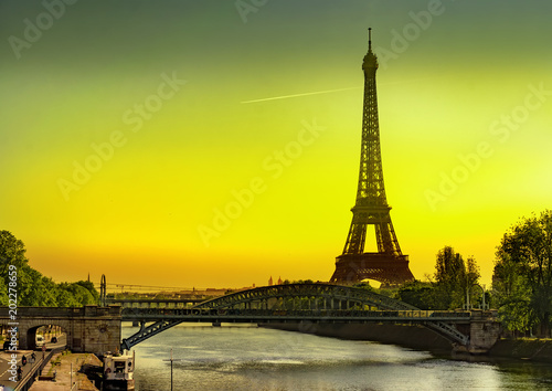 Leinwanddruck Bild The Eiffel Tower and Cygnes bridge over river Seine at sunrise in Paris, France