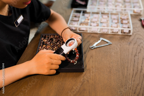 Hands of female jewelry designer looking at her work with magnifying glass © makistock