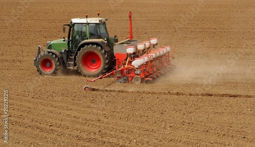 Aluminium Trekker Tractor with a modern sowing seeds machine in a newly plowed field in springtime. Side back view, with only plowed land as a background