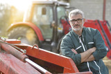 Farmer standing by tractor outside the barn - 202293253