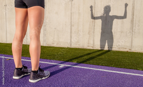Silna sportowa kobieta na stadium bieg śladzie podczas słonecznego dnia