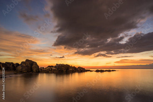 Amazing colorful sunset with clouds on sky and rocks in water on Phu Quoc Island in Vietnam
