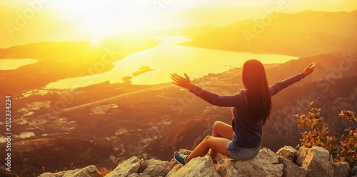 Wall mural Happy woman in the mountains looking at the sunset