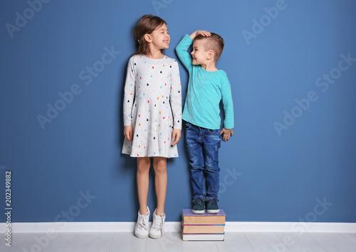 Leinwandbild Motiv Little girl and boy measuring their height near color wall