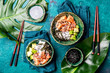 Hawaiian salmon poce with avocado, rice and sesamo served in bowls on tropical leaves. Turquoise slate background. Top view
