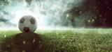 Fußball liegt auf Stadionrasen im Rauch - 202370406