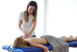 Young physiotherapist doing a back treatment to the patient in a physiotherapy room. - 202371608