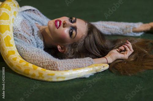 Beauty model with makeup face and yellow serpent. Sensual woman relax with albino python. Snake crawl on woman with long hair. Danger temptation and desire concept © tverdohlib