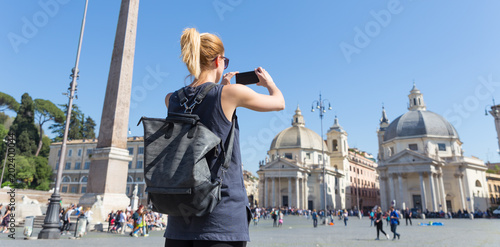 Female tourist with a fashinable vintage hipster backpack taking photo oof Piazza del Popolo, People's Square, in Rome, Italy by her mobile phone.