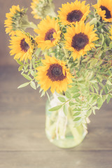 Bouquet of bright sunflowers in a glass jar on a wooden table. Retro toned.