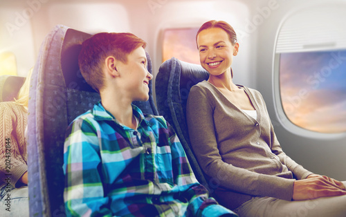 travel, tourism and family concept - happy mother and son sitting in plane and talking over porthole background