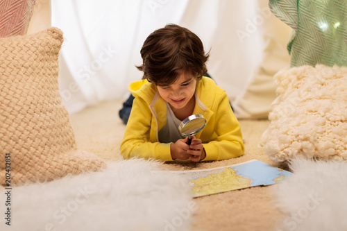 childhood, travel and hygge concept - happy little boy with magnifier and road map searching location in kids tent at home