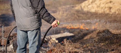 A man extinguishes the burning grass with water