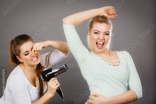 Woman drying friend armpit with hair dryer
