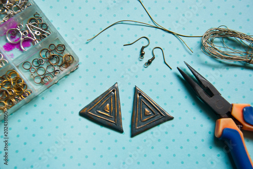 Working process jewelry making assembly ethnic green earrings from polymer clay. Hobby, handicraft.