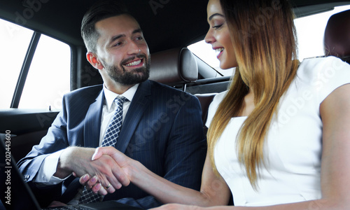 Business people shaking hands, finishing a meeting in the car