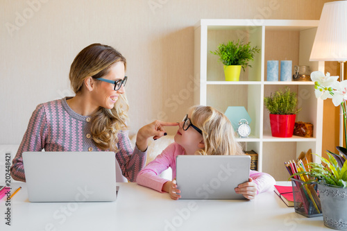 Foto Murales Mother and daughter sitting at table and using computers together
