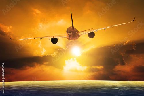 passenger plane flying over beautiful sunset sky