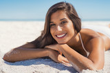 Smiling woman lying on sand - 202458263